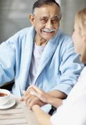 Nurse and senior patient sitting at table Stock Photos