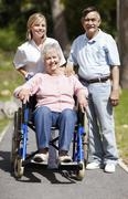 Nurse pushing senior woman in a wheelchair Stock Photos