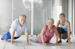 Senior couple exercising with a fitness instructor Stock Photos