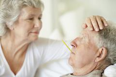 Senior woman caring for man with a fever Stock Photos