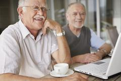Two senior men relaxing at table Stock Photos