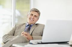 Stock Photo of Portrait of cheerful businessman with laptop