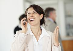Stock Photo of Cheerful businesswoman using mobile phone