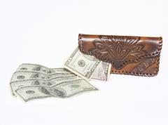 women's wallet next to a few dollar bills - stock photo