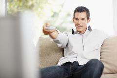 Mid adult man in front of televisionchanging channels - stock photo