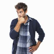 Stock Photo of Studio shot of young man biting nails and looking away