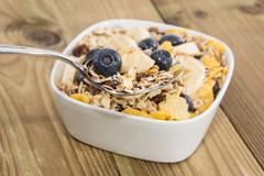 muesli on a spoon with bowl in background - stock photo