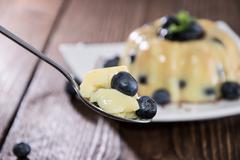 spoon with pudding and blueberries - stock photo