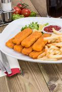 Plate with chips and fish fingers Stock Photos