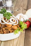 Stock Photo of bowl filles with kebab meat on wood