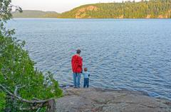father ans son enjoying the wilderness evening - stock photo