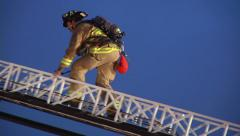 Firefighter Climbs Up Aerial Ladder On Fire Truck 1 Stock Footage