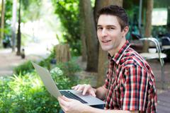 Portrait of young man with laptop outdoor Stock Photos