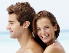 Young attractive couple enjoying summer holiday on beach Stock Photos