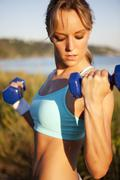 Woman lifting weights outdoors - stock photo