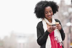 Stock Photo of USA, Washington State, Seattle, Cheerful young woman text messaging while