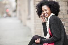 Stock Photo of USA, Washington State, Seattle, Cheerful young woman using mobile phone