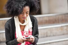 Stock Photo of USA, Washington State, Seattle, Cheerful young woman text messaging