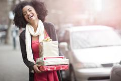 Stock Photo of USA, Washington State, Seattle, Young cheerful woman carrying stack of boxed