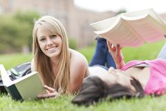Stock Photo of Two female college student lying on grass reading books, one looking at camera