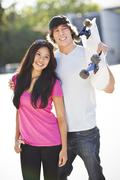 Stock Photo of Young multi-racial couple posing with skateboard