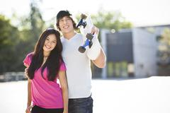Young multi-racial couple posing with skateboard Stock Photos