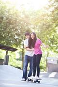 Young multi racial couple skateboarding Stock Photos