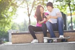 Young multi-racial couple sitting with skateboard, using mobile phone Stock Photos