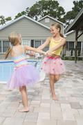 Girls in tutus playing by swimming pool - stock photo