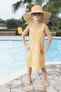 Sassy girl standing at edge of swimming pool Stock Photos
