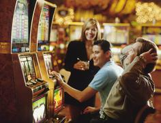 People in casino playing on slot machines - stock photo