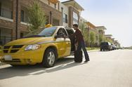 Stock Photo of USA, Texas, Dallas, Man alighting from taxi