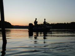 Silhouette of fisherman on boat at sunrise Stock Footage