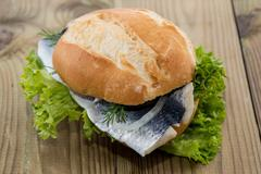 fresh herring on a roll (wooden background) - stock photo