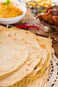 Chapatti roti and indian food on dining table. Stock Photos