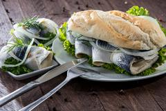 herring filet on a baguette (against wood) - stock photo