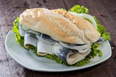 Stock Photo of fresh herring with onions on a baguette