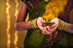diwali or deepavali photo with female holding oil lamp during festival of lig - stock photo
