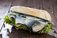 fresh herring with onions on a baguette - stock photo