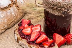 bread with strawberry jam (rustic background) - stock photo