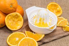 squeezer with fresh oranges - stock photo