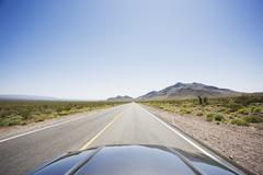 Car driving on highway through the desert - stock photo