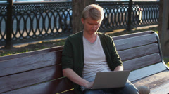 Man in park working laptop reading and writing messages browsing Stock Footage