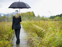Stock Photo of Person walking on boardwalk on rainy day