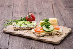 cutting board with crispbreads and herbs - stock photo