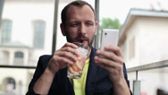 Stock Video Footage of Young man with smartphone drinking cocktail in bar HD