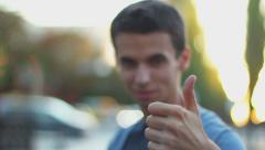 Young man thumb up, like, thumb-down, dislike gestures, wants Stock Footage