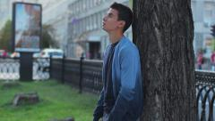 Young adult with headache in park, problem, pain, relationships Stock Footage