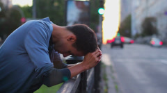 Young adult depression, heart break standing fence traffic cars Stock Footage