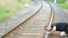 Man laying on the railroad tracks Stock Footage